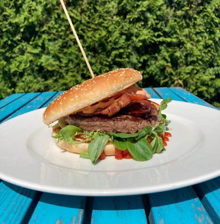 Burger wołowy Bacy z grillowanym serem wędzonym i boczkiem oraz pomidorem i smażonymi krążkami cebulowymi