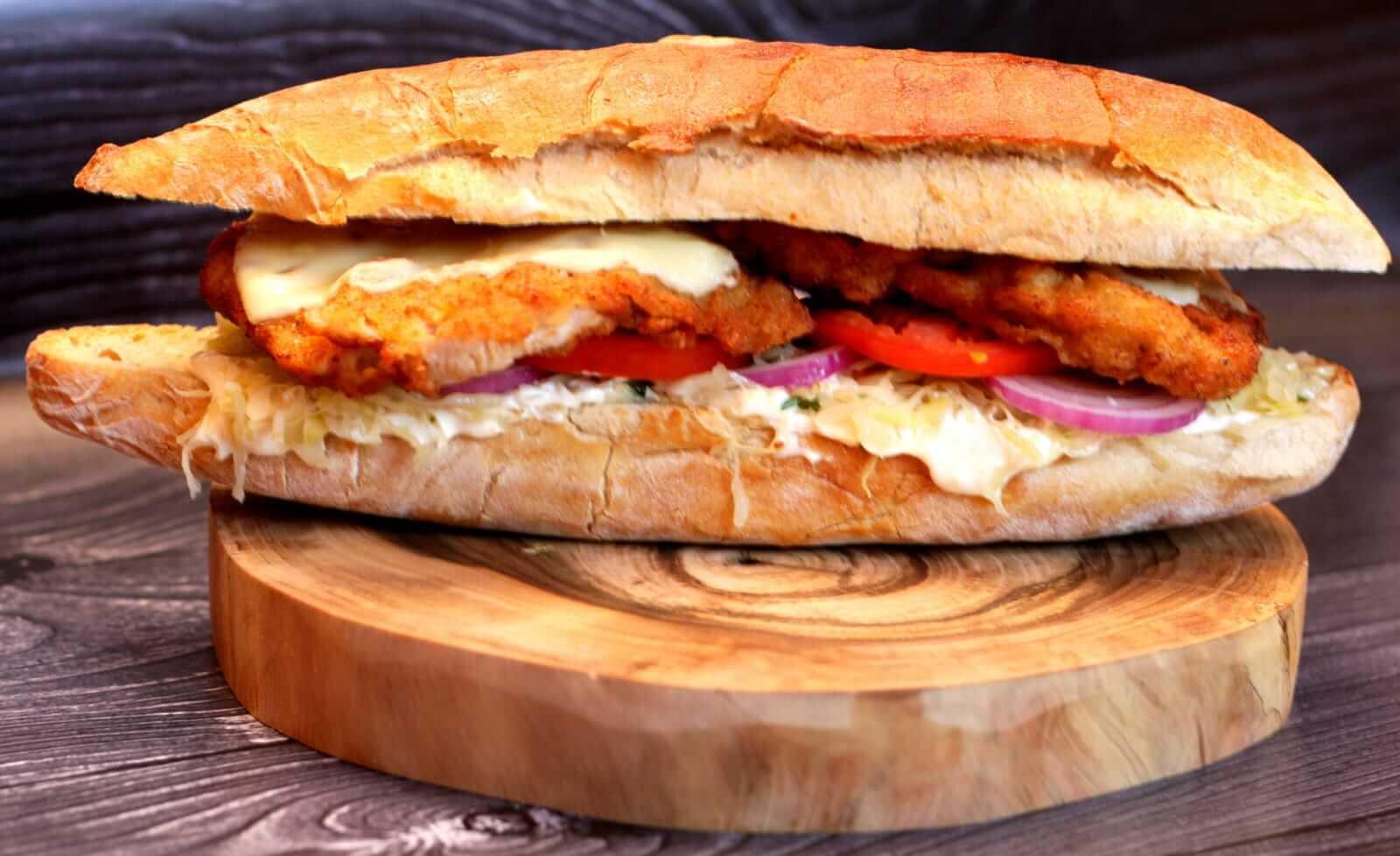 Kotleto burger - kukiełka lisiecka z chrupiącym kotletem schabowym, serem żółtym, kapustą kiszoną, cebulą, pomidorem i sosem majonezowo-chrzanowym