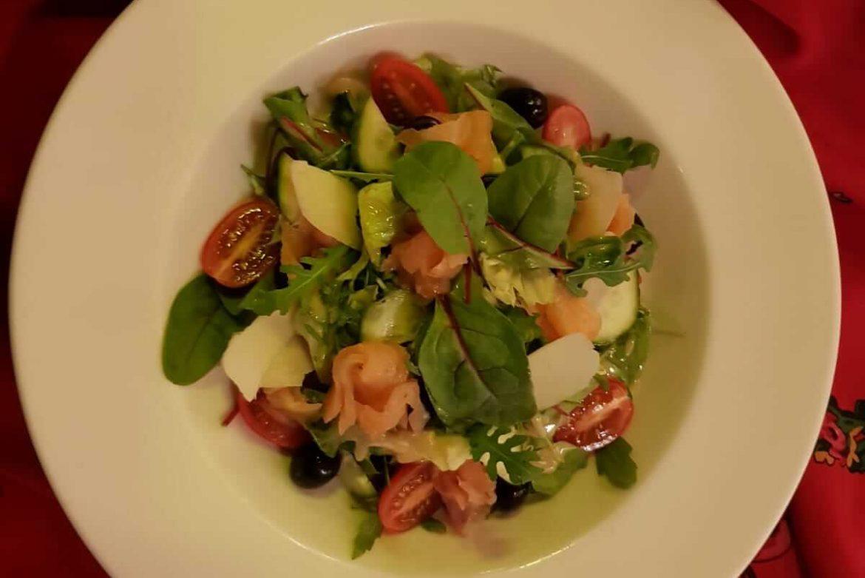 Mix sałat z łososiem wędzonym, pomidorem, ogórkiem, czarnymi oliwkami, parmezanem i sosem winegret